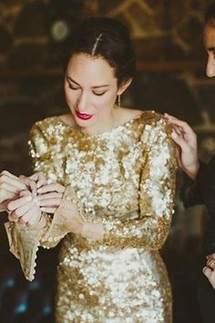 A bride wearing a gold sequined wedding dress and bright red lipstick.