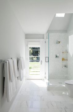 Natural light shines in through a skylight situated in the sloped ceiling above walk in shower boasting white mosaic wall tiles fitted with a polished nickel sh. Attic Shower, Small Attic Bathroom, Master Bathroom Shower, Pool Bathroom, Bathroom Design Small, White Bathroom, Bathroom Interior, Bathroom Ideas, Industrial Bathroom