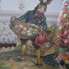 Dressed in his Sunday best, this proud Papa Bunny is getting ready for Easter as he unloads baskets filled with colorful eggs from his wagon. This nostalgic table top display is not only festive but also, will add some sparkle and cheer to your holiday decor! Add a pink 'bottle brush' Easter tree and/or a foil wrapped bunny, to complete the scene.