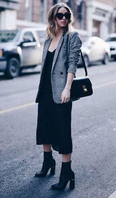 O vestido midi preto é peça curinga e total chic. Ele pode ser usado no office look, na balada e em todas as ocasiões. O blazer xadrez que é muito tendência complementa o outfit. it-girl - vestido-preto-blazer-xadrez-bota - blazer xadrez - inverno - street style