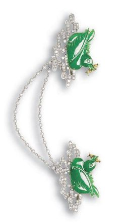 A pair of jadeite and diamond brooches Each brooch comprising a mandarin duck carved from lively emerald green material of good translucency, with a yellow gold fish set with yellow-tinted diamonds in its beak, floating atop pavé-set diamond ripples, accompanied by a detachable collet-set diamond chain that may be used to link the pair of brooches together, mounted in platinum and 18k yellow gold,