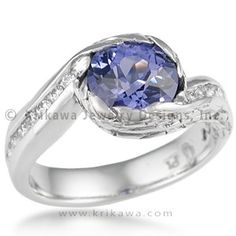 Wings of Love Engagement Ring - Let your love spread its wings! This asymmetrical engagement ring design is named for its hand engraving of feathers and wingtips, and was derived from the Carved Wave. The round center gemstone or diamond sits snugly in the engraved bezel. The band has channel-set diamonds or sapphires extending halfway down (0.18 carat total weight), and measures 4mm wide on the palm-side. Consider graduated color in your ring's channels! Exquisitely handcrafted in your…
