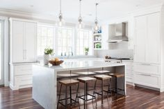 lovely, light-filled white kitchen with marble island, rustic wood and steel bar stools by Threshold Goods & Design