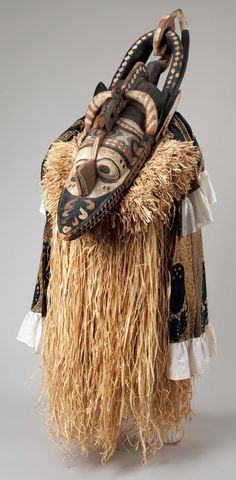 Africa | Mask (Banda) from the Nalu peoples, Niger River region, Guinea. | Wood, paint | 19th - 20th century | The raffia and textile attachments that can be seen on this mask have been reconstructed in 1995. | In contemporary Baga society, the Banda performer, invariably a young man, carries the wooden headdress on top of his head. Attached to the underside of the headdress is a large raffia cape that covers the dancers face and extends to his knees.