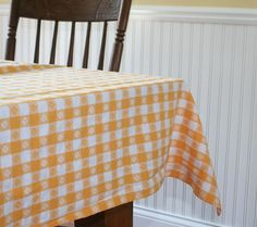 This sunny yellow gingham check tablecloth measures 56 x 52. Made of cotton, it…