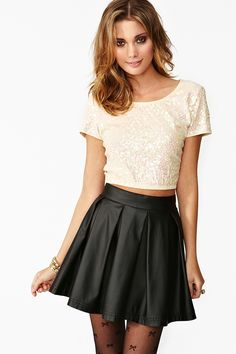 crop tee and leather A-line pleated skirt. The bow tights add a flirty, girly element to the whole outfit