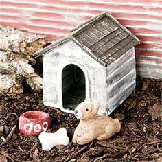 A quaint white dog house complete with doggy friend, dish and bone!