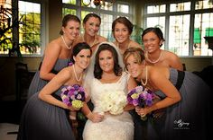 Bride with her bridesmaids dressed in gray and holding bouquets in shades of purple.  Photo by Brian McGarry.