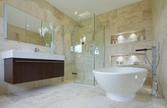 Warm beige marble flooring and walls wrap this bathroom, featuring floating dark wood vanity across from white pedestal tub, with glass shower stall in corner. Built-in wall coves are internally lit, with patterned tile backing.