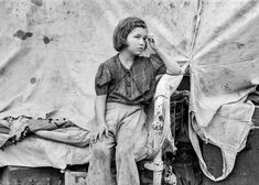 """1939. """"Child of migrant worker sitting on bed in tent home of cotton picking sacks, Harlingen, Texas."""" Photograph by Russell Lee."""