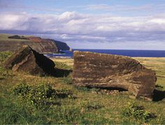 Many toppled moai were deliberately decapitated by having stones placed in the path of their fall. Here, pieces of a fallen moai frame the distant re-erected statues of Tongariki.
