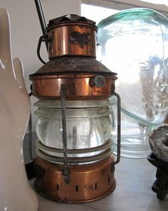 vintage nautical lanterns hung from hook on wall as bedside lamps