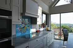 This wonderful glass panel is one of our bespoke glass kitchen splashbacks, and it was created for and delivered to a lovely home in Sturton by Stow, Lincoln. The design of the piece is a stunning flower burst, created on a beautifully blue background of enamel powder. Each petal of the flower burst was carefully cut down to size from a variety of colours and textures that both contrast and complement the sky blue base.