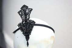Miss Fisher wears this headpiece in 'Death Comes Knocking' (Series 2, Episode 2). The original item was an existing headpiece, however the assistant designer had to recreate a second one for a stunt double to wear. He found shoes in an op shop with similar beading and made a copy of the original from the shoe detail. #MissFisher #PhryneFisher #accessories #jewellery #headpiece #fashion #style #costume #1920s