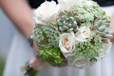 Succulents! I'm thinking of something like this with the roses a little peach-ier, and a navy ribbon...