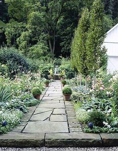 Kevin planted pots of boxwood and a loose, informal mix of nicotiana, sweet alyssum, and dahlias in the two beds flanking the stone path.   - CountryLiving.com