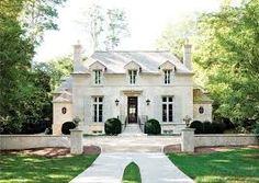 French exterior.  narrow windows, hip roofing, light neutral exterior paint, dark wooden door.