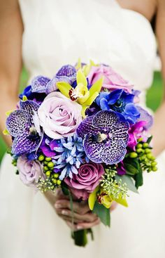 Toss-up on where to pin this unique bouquet ... freckled vanda orchids, bright chartreuse cymbidium orchids and hypericum berries, electric blue anemones, light blue agapanthus and lavender roses.