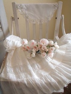 An antique highchair, christening gown, and doily, displayed with sweet pink roses.  Perfection.