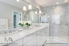 White and gray master bathroom with gray walls framing white double vanity and marble countertops with his and her sinks.