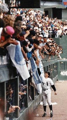 White Sox catcher Carlton Fisk reaches out to fans following the last game at the old Comiskey Park on Sept. 30, 1990.