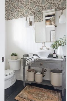 Lovely white and gray cottage style powder room features an orange vintage rug placed on dark gray slate floor tiles in front of a distressed gray bat. Wainscoting Bathroom, Bathroom Wallpaper, Bathroom Floor Tiles, Bathroom Vanities, Sinks, Vanity Mirrors, Grey Slate Floor Tiles, Slate Flooring, Gray Floor
