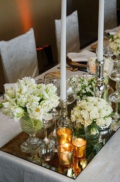 White tulips and roses in textured glass vases are reflected in a mirrored table runner.