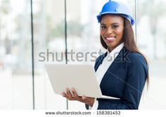 attractive young african architect using laptop in office