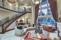 Floor-to-ceiling+windows+enhance+the+grandeur+and+height+of+this+traditional+great+room,+just+off+the+foyer.+A+wrought+iron+stair+railing+nods+to+the+Mediterranean+architectural+design+of+the+home.