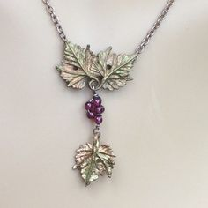 """Artisan made grape leaf pendant 🎉Essential Style & Total Trendsetter HP🎉 Beautiful greenish gold colored grape leaf pendant. Tiny purple beads represent grapes. 16"""" chain with lobster clasp. Don't know what kind of metal this is. This is an art piece. Perfect for any wine lover! Boutique Jewelry Necklaces"""