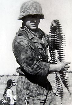 A Waffen-SS Grenadier in full M44 DOT camouflage uniform grabs a belt of linked 8mm ammunition for the MG42 machine gun. An excellent uniform study demonstrating the high degree of issue of camouflage uniforms and patterns in the German military during WW2. The Waffen-SS had distinctive camouflage patterns but used the same equipment as Wehrmacht forces. The lie over the years was they were better equipped. They were not.