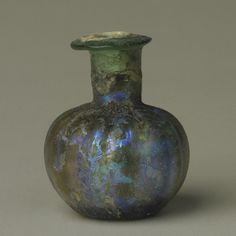 This Roman glass jar was originally clear. Over the years, water and atmospheric pollution have created many thin layers of glass on the outside of this object, which has given it an attractive metallic sheen or iridescence. Accession number 1977.113.45