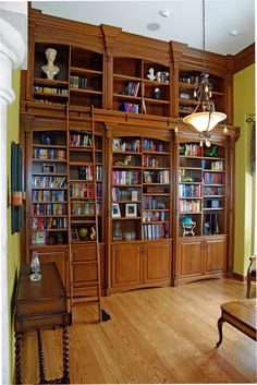 These custom floor-to-ceiling bookshelves are any bibliophile's dream and a sophisticated addition to any study or living space. We love the combination of colorful book covers, richly stained wood, and decorations the customer placed throughout their shelves - and with plenty of room to expand that beautiful library!  #rolling #ladder #stained #shelves #cupboard #den #office #reading #high #ceiling