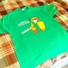 Legend of Zelda T Shirt Mens Large . Clean logo with very light wear . Vintage Zelda green . Old Style Zelda logo . Looking for a new home with a video game enthusiast. Tops Tees - Short Sleeve