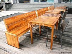 Lasierte Holztische und Holzbänke auf alten Schiffsdielen vor einem Restaurant am Hafen von Münster in Westfalen