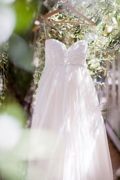 Strapless wedding gown hanging in the trees @myweddingdotcom