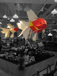 giant paper goldfish swims trough the air