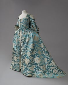 Robe à la francaise, 18th century. Chinese cerulean blue silk woven with a large-scale white and platinum floral, self buttons, trimmed with furbelows edged in silk fly braid, bodice lining in various cottons, the front printed in a red windowpane.