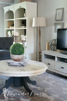 Modern Farmhouse Living Summer Home Tour/living space with round coffee table and white bookshelves