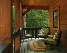 front porch of log home, cozy furniture for front porch, front porch in a wooded setting, black handrails on a porch, small log cabin in the woods, small log cabin, small log home, log homes, log home with porch, cozy log home, log home with black roof, Timberhaven log homes, engineered log homes, log home designs