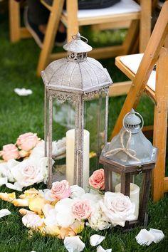Lanterne e fiori chiari. Un modo romantico di decorare lo spazio della cerimonia. I toni anticati del ferro donano un tocco retrò. #Dalani #Shabby #Wedding