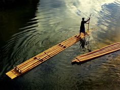 A boatman paddles his bamboo raft along the river at Wawa Dam, Philippines © Gerardo Sabado