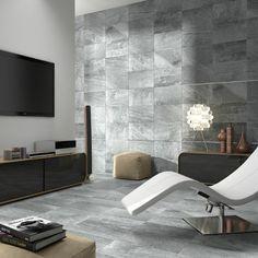 salon avec carrelage gris mural et de sol, chaise longue blanche, commode en bois sombre laqué et tabourets en beige