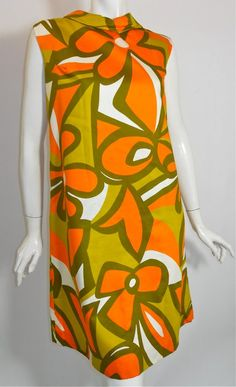 60s polished cotton oversized, abstract floral print shift dress in bright orange, greens and white. Foldover collar, sleeveless, wide cut.