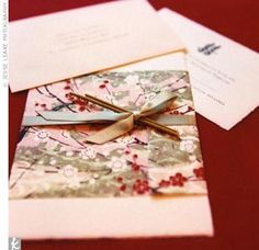 """""""Our wedding invitation was the starting point in reflecting our cultures,"""" says Jodie. The couple's invites combined Japanese and Chinese elements with a colorful Japanese washi paper wrap, and featured celadon green paper and red flowers on the outside and the Chinese """"double happiness"""" character in green on the inside. """"My father-in-law asked th ..."""