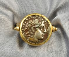 FINE JEWELRY - SALE 2601B - LOT 131 - HIGH-KARAT GOLD AND ROMAN COIN SWIVEL RING, JANIYE, THE BEZEL-SET ROMAN COIN JOINED TO A SQUARE SHANK, APPROX. SIZE 7, SIGNED. - Skinner Inc