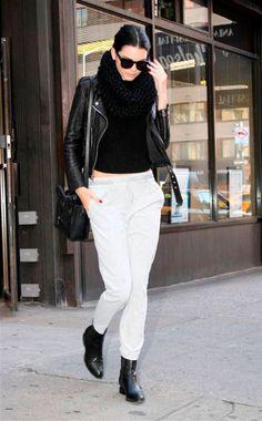 Street style look Kendall Jenner calça de moletom branca, blusa preta canelada, gola tricot e, bota e jaqueta de couro.