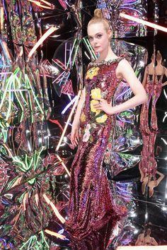 """In die groteske Welt der Mode entführt der neue Film """"The Neon Demon"""" von Regisseur Nicolas Winding Refn. Schauspielerin Elle Fanning spielt in dem Thriller die Hauptrolle. Zur Filmpremiere erscheint sie in einem Glitzerkleid mit Blumen-Applikationen von Dolce & Gabbana."""