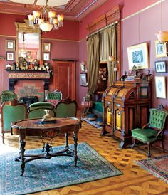 Parquet wood floor, green and dark wood furniture, and magenta(?) walls.