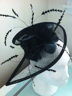 Black races fascinator made from sinamay for wedding or cocktail events with flowers and arrow feathers mounted on a headband